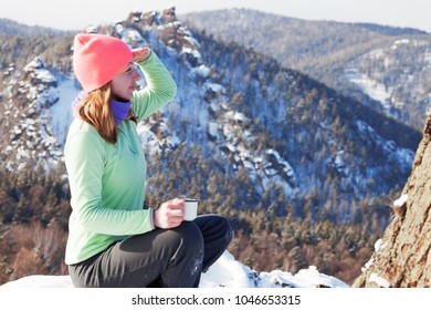 cheerful girl on a hike in the mountains in winter