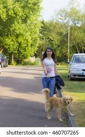Cheerful girl on walk with golden retriever (focus on girl)