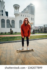 cheerful girl in orange hoodie fast rides on the street on a longboard and laughs