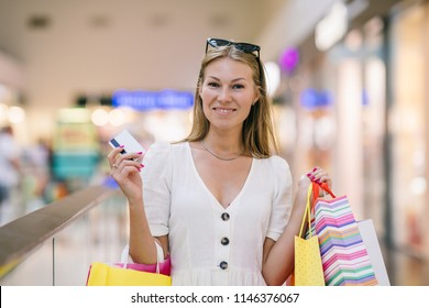A cheerful girl with a phone, a bank card and shopping in the mall. Quickly and easily make an order online, pay, get a profitable offer