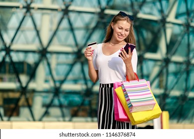 Cheerful girl with a phone, a bank card and shopping at the mall. Quickly and easily make an order online, pay, get a profitable offer