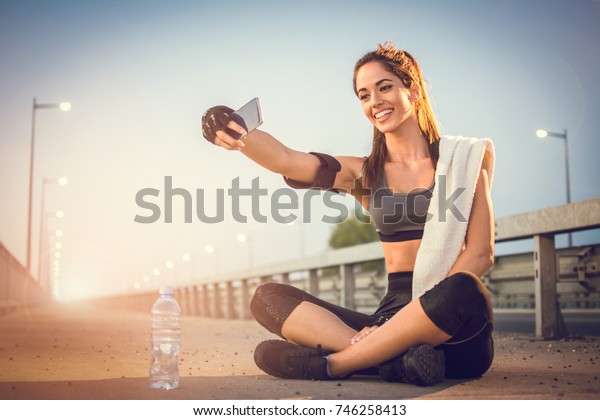 Cheerful girl with phone taking selfie photo for social media after running outdoors.