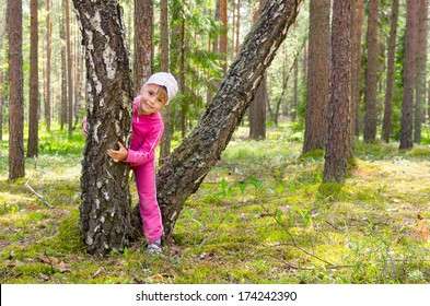 Cheerful girl plays in a forest glade.
