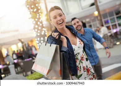 Cheerful girl pulling on boyfriend's arm to go shopping