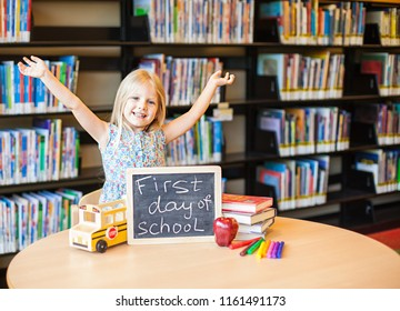 Cheerful girl raising hands at the table with chalkboard, books, markers and apple on it. First day of school
