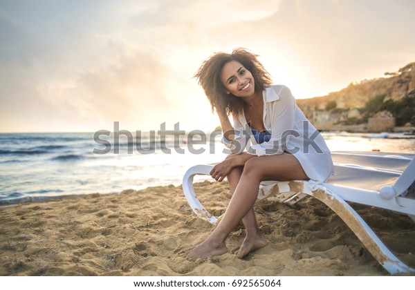 Cheerful girl relaxing at the beach. She is sitting on a sunbed.