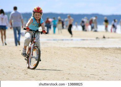 Cheerful girl riding with bicycle along the beach