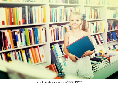 Cheerful girl in school age holding chosen book in hands in bookstore