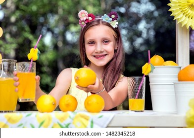 Cheerful girl sells lemonade on the street in the park