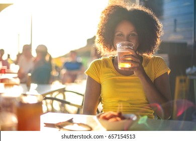 Cheerful girl sitting in a bar, drinking beer