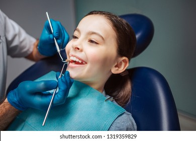 Cheerful girl sitting in dental chair in room. She show teeth. Dentist doing check-up with small mirror and tool.
