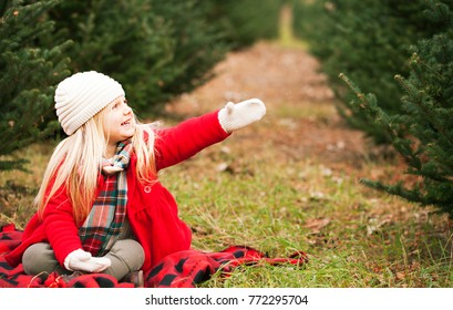 cheerful girl sitting on blanket – Christmas time