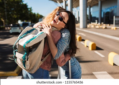 Cheerful girl in sunglasses happily hugging her female friend with backpack outdoor near airport