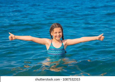Cheerful girl swims in the sea. Child shows thumbs up sign. Smiling girl likes the sea and the beach. Happy summer holiday, summer vacation concept. Summer fun.