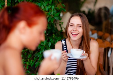 cheerful girl talks to her friend, over a Cup of coffee, in a cafe, in the open air, on a Sunny day