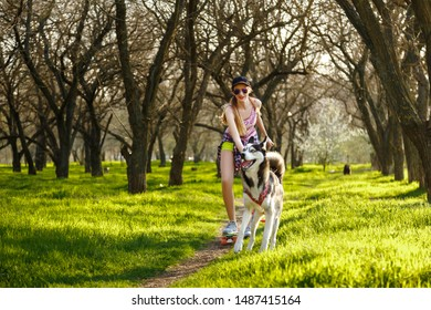 A cheerful girl in a T-shirt, shorts, sneakers, glasses and a cap, with a skateboard in her hands, walks in the park with a husky dog. Summer rest