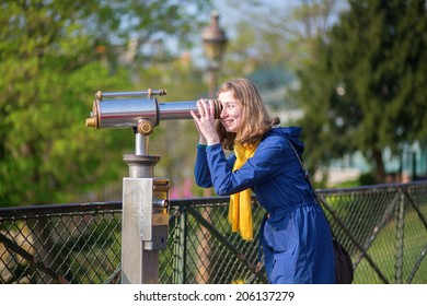 Cheerful girl using telescope for sightseeing in Paris
