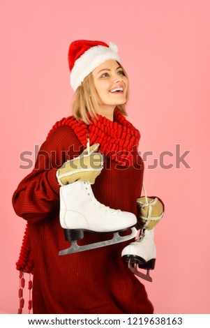 90076e59148 Cheerful girl in warm sweater and hat with figure skates. Woman at ice- skating