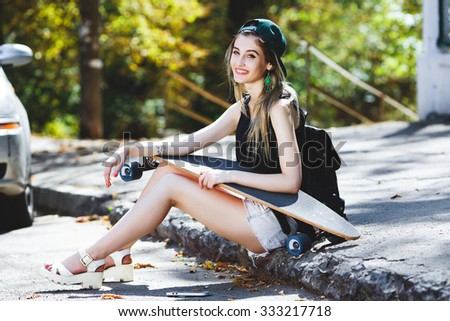 Cheerful girl, wearing in cap, shirt, sandals and shorts, with backpack, sitting on the pavement with skateboard and looking at camera, on the street, full body