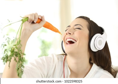 Cheerful girl wearing headphones singing using a carrot as a microphone at home