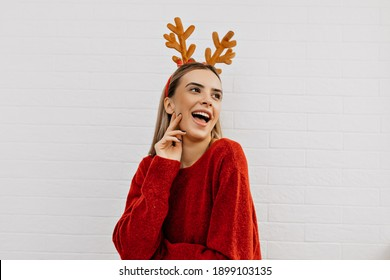 Cheerful girl wears christmas headgear smiling and having fun over isolated background. Studio photo of woman red sweater. High quality photo