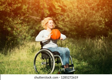 Cheerful Girl In Wheelchair Is About To Throw A Basket Ball. Recovery Concept, Disability And Sport