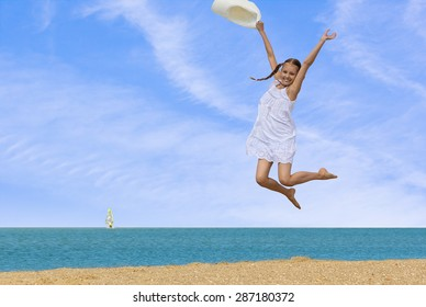 Cheerful girl in a white sundress and a white hat in his hand  jumping over the water on the beach against the sea and blue sky with clouds on a hot summer day