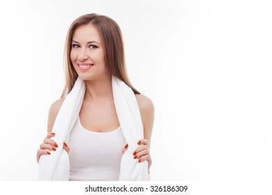 Cheerful girl is wiping neck with white towel after training. She is standing and holding towel. The lady is looking at camera with joy and smiling. Isolated and copy space in right side
