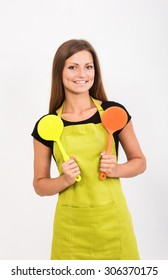 Cheerful girl in yellow apron with two spatulas