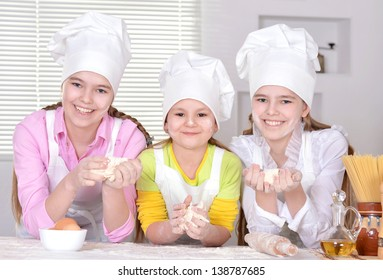 cheerful girls cook the dough for the cake in the kitchen