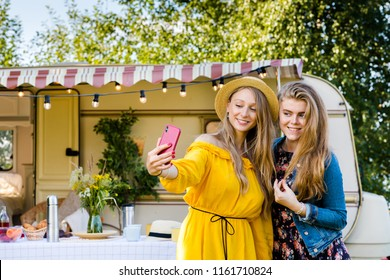 Cheerful girls do selfie on a smartphone on the back of a van in a camping. Road trip with best friends. Adventure, freedom, youth