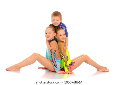 The cheerful girls are gymnasts, and the little boy of their brother hugs together. The concept of fitness and sports, a happy childhood. Isolated on white background.