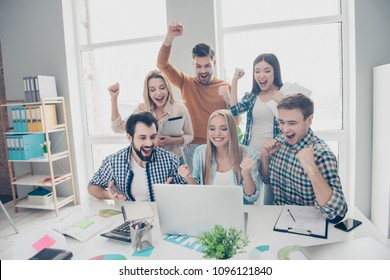 Cheerful, glad, joyful, lucky, stylish, positive, attractive business people looking at screen of laptop with raised hands shouting yelling celebrating successfully completed project, enjoying results