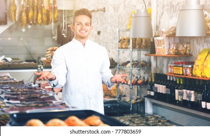 Cheerful glad shop assistant in grocery shop greeting customers