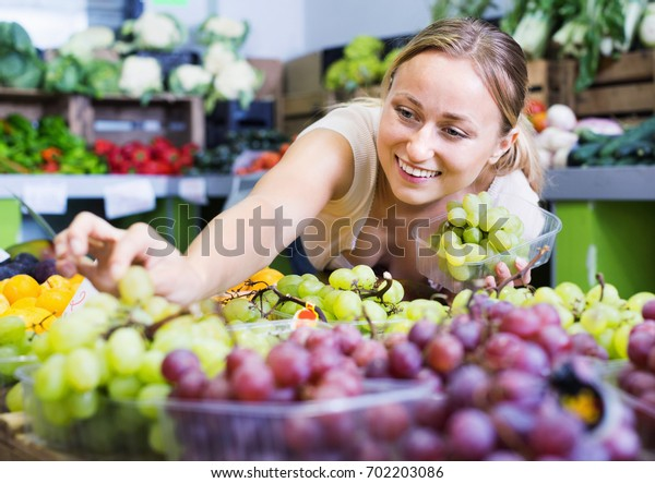 Cheerful glad  young woman customer buying sweet ripe grapes on marketplace