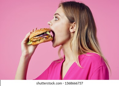 Cheerful glamorous woman in a pink shirt with a hamburger in the hands of a fast food diet