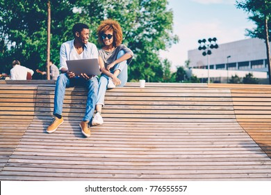 Cheerful good looking best friends dressed in stylish clothing laughing and joking during recreating outdoors.Positive female in sunglasses and smiling male having recreation time at sunny day
