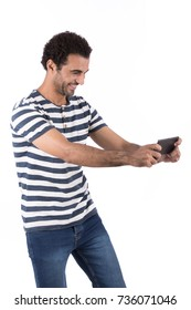 Cheerful good looking man playing a video game on his smartphone. Isolated on white background.