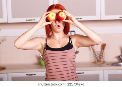 Cheerful good morning in the kitchen. Young woman closes her eyes with apples. Girl holding a red apple. Laughter and joy, smile, diet, healthy, nutrition, fruits, youth, beauty. Concept of lifestyle.