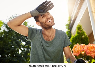 Cheerful good-looking young caucasian man in blue t-shirt and gloves smiling with teeth, being tired from hard work in garden. Farmer planting leaves in countryside house