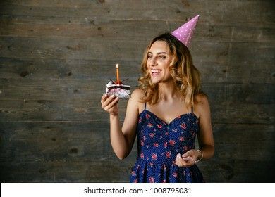 Cheerful gorgeous young woman looking at birthday chocolate cake with candle while celebrating her birthday, wearing festive hat.