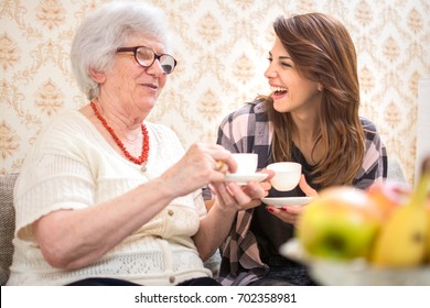 Cheerful granddaughter and her grandmother having together coffee cups at home.