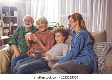 Cheerful grandfather, beaming granny, outgoing boy and glad lady relaxing on sofa. Child using appliance. Rest and family concept