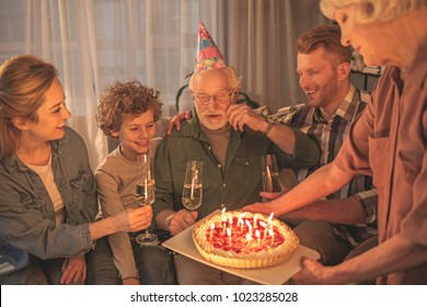 Cheerful grandfather celebrating birthday with beaming family . He looking at pie. Party concept