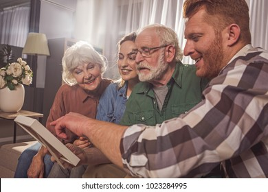 Cheerful granny, glad female with interested grandpa and smiling male watching at photo. Entertainment concept