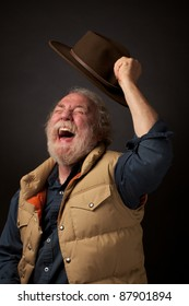 Cheerful gray bearded senior man shouts with joy and waves his hat in the air. He wears a down vest and blue denim shirt. Dark background and horizontal composition with copy space.