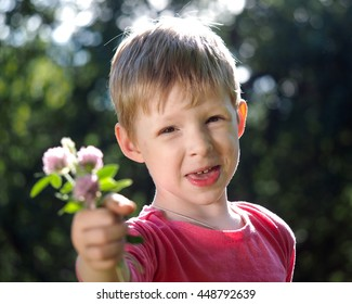 Cheerful grimy kid with a bouquet of flowers. The concept of happiness of the child, summer, greetings
