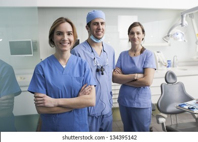 Cheerful group of dentists and their assistants standing in the dental office and looking at camera.