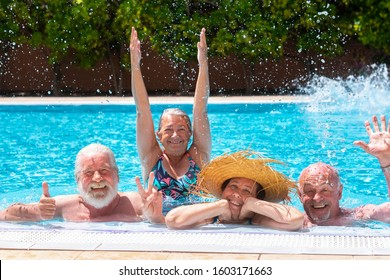 Cheerful group of four senior people floating in outdoor swimming pool raising splashes of water. They smile relaxed on vacation under the bright sun