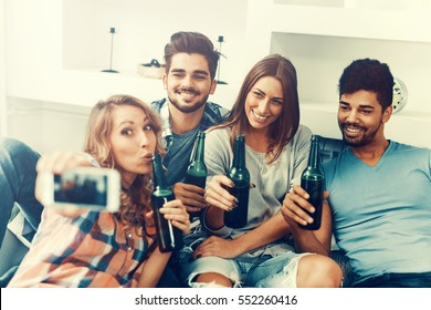 Cheerful group of friends having fun at home,taking selfie.